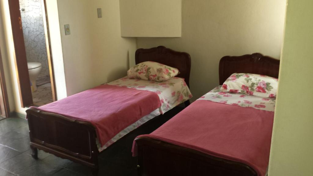 A bed or beds in a room at Pousada Chico Taquara