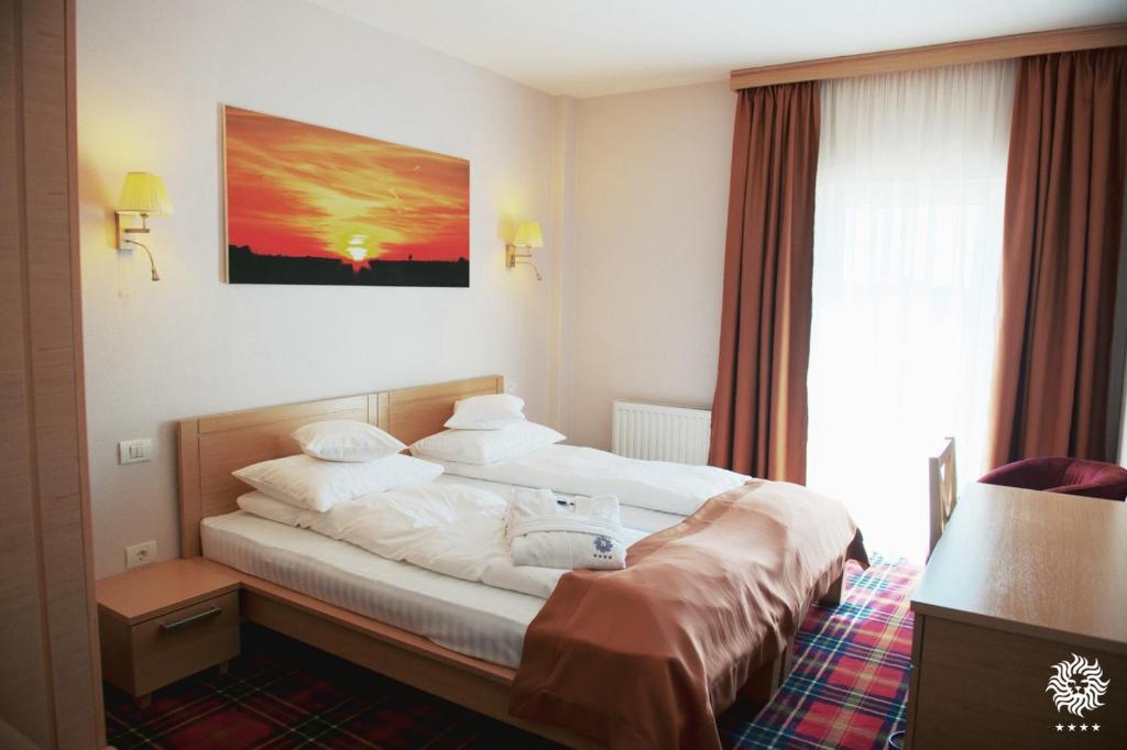 Un pat sau paturi într-o cameră la Hotel Leon & Spa