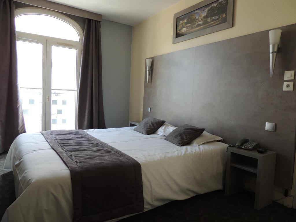 Un ou plusieurs lits dans un hébergement de l'établissement Hôtel Le Home Saint Louis