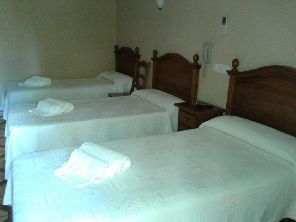 A bed or beds in a room at Hostal Ginebra