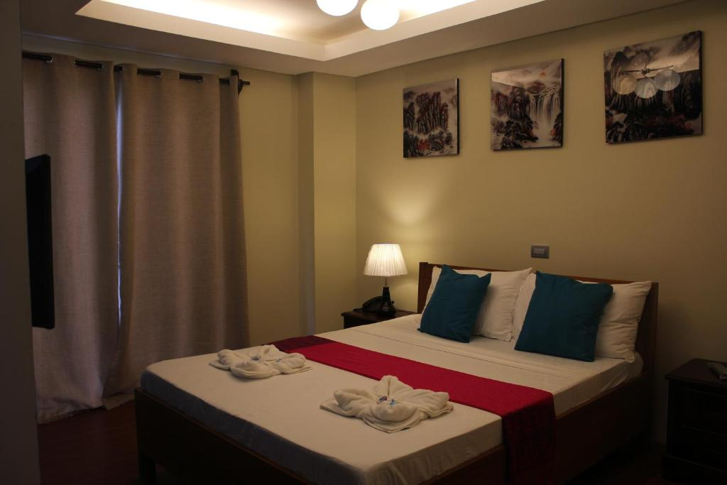 A bed or beds in a room at Aqua Travel Lodge
