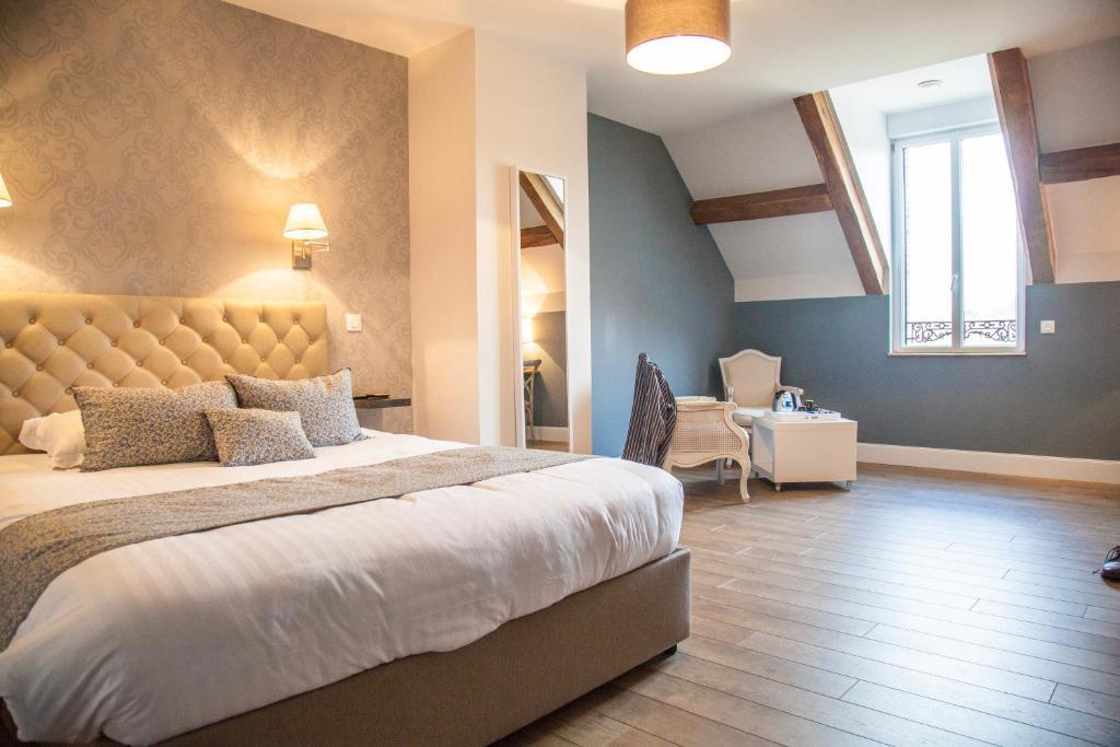 Un ou plusieurs lits dans un hébergement de l'établissement Hotel The Originals Auberge du Moulin à Vent (ex Relais du Silence)