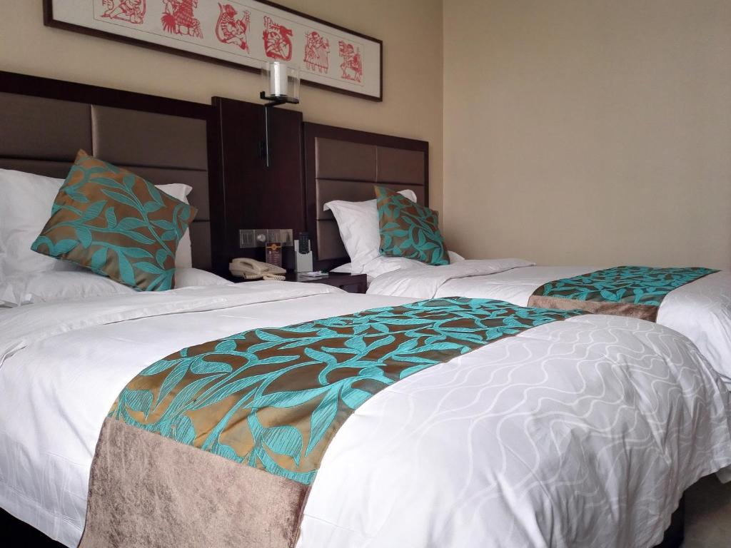 A bed or beds in a room at Shanxi Quanjin Business Hotel
