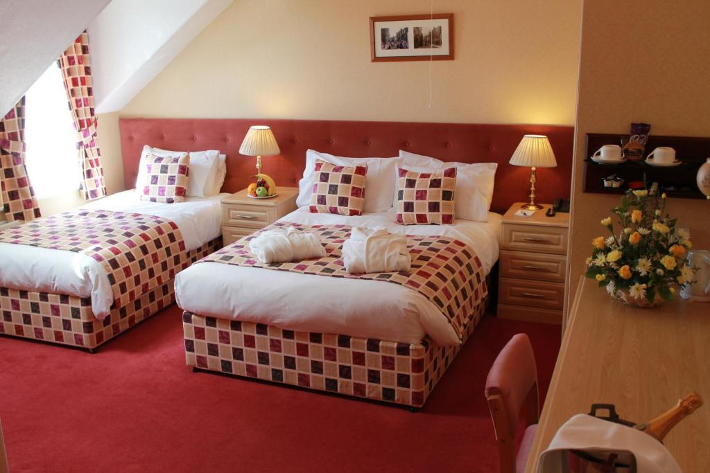A bed or beds in a room at Saxonville Hotel