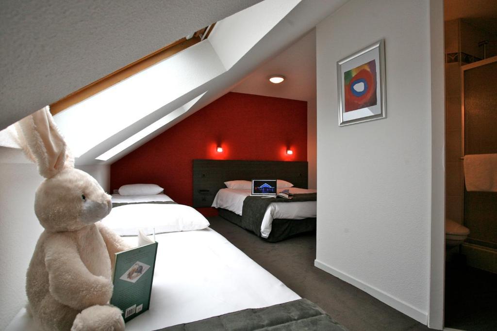 Un ou plusieurs lits dans un hébergement de l'établissement Kyriad Saint Brieuc - Tregueux