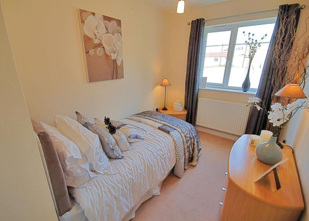 A bed or beds in a room at Bridlington Holiday Cottages