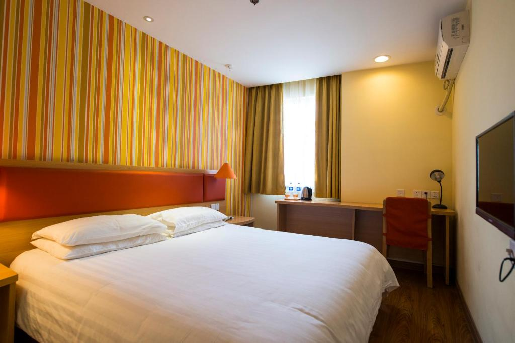 A bed or beds in a room at Home Inn Shanghai Pudong Zhoupu Kangqiao Town Xiuyan Road Industrial Park