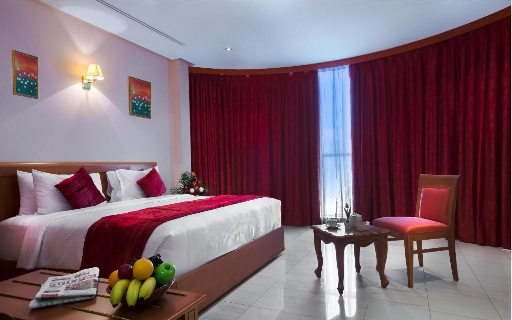 A bed or beds in a room at Al Madina Suites Doha