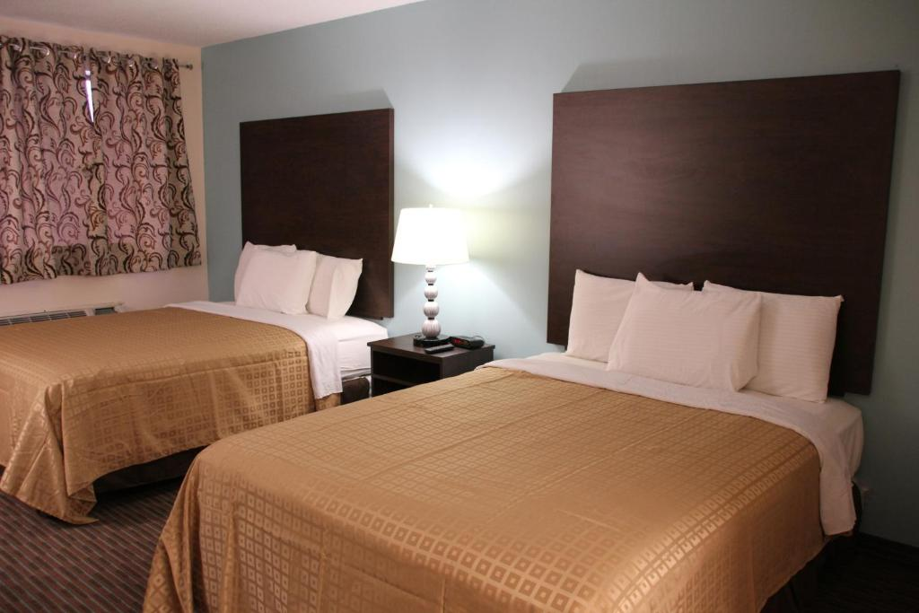 A bed or beds in a room at Sterling Inn near IAG Airport