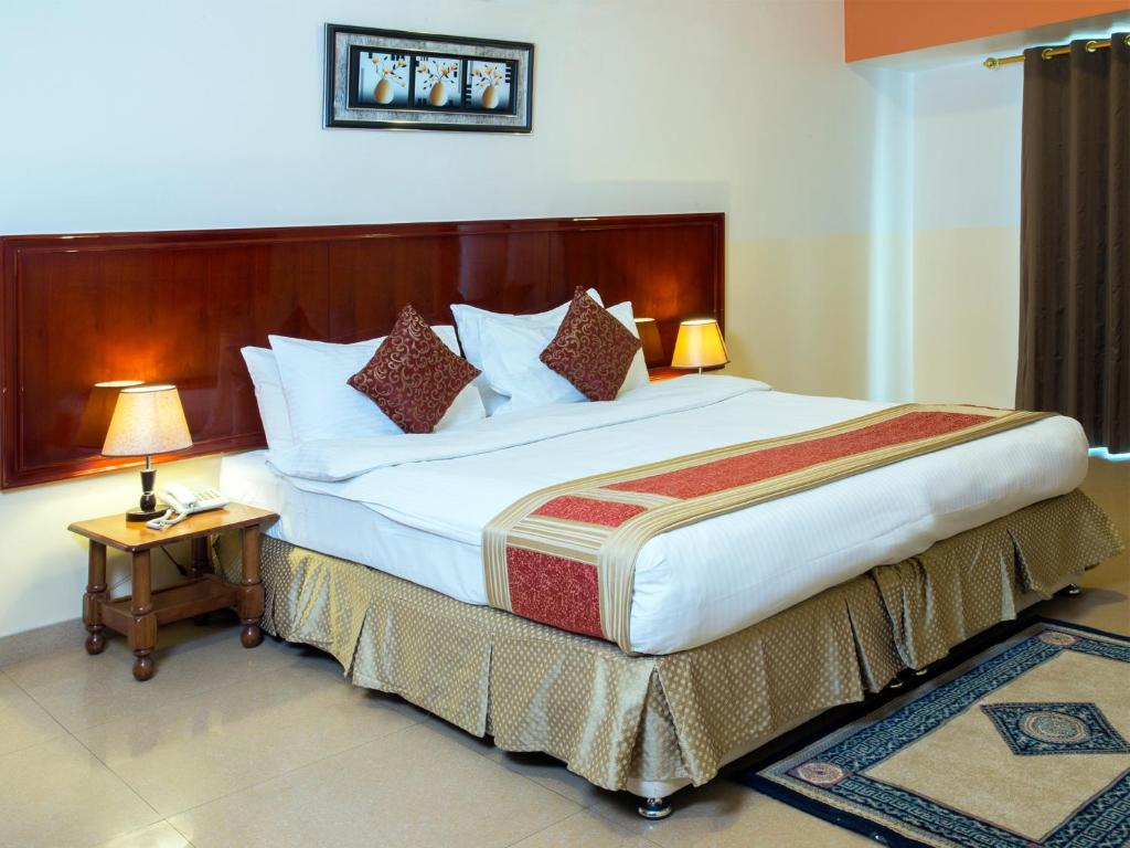 A bed or beds in a room at Safeer Plaza Hotel Apartments