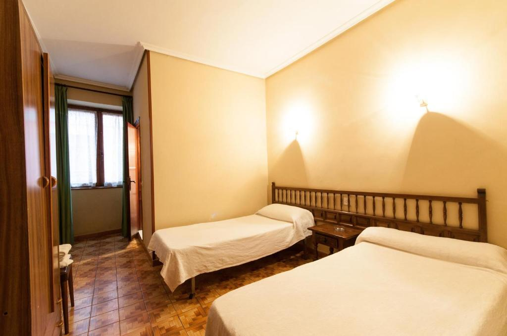 A bed or beds in a room at Pension Iberia