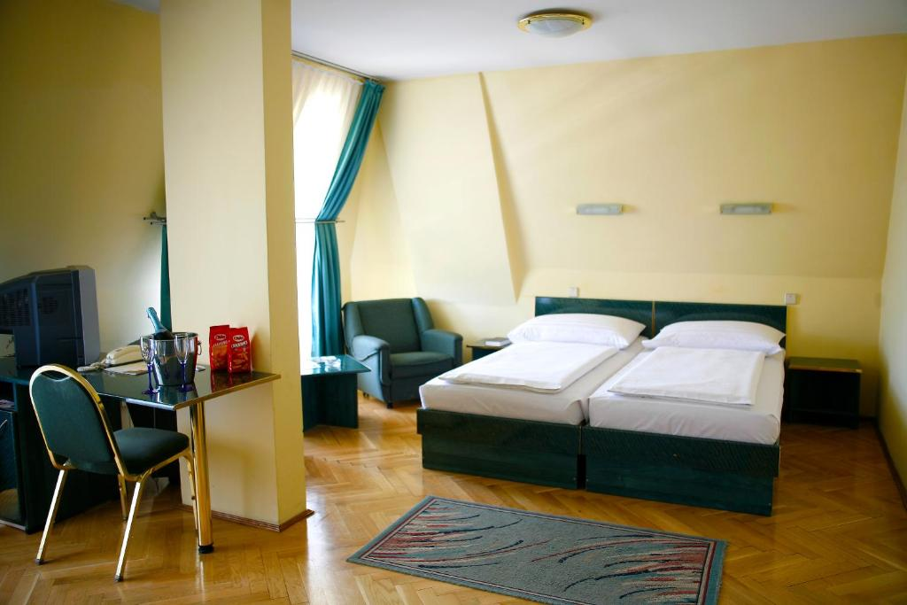 A bed or beds in a room at Hotel Bara Budapest