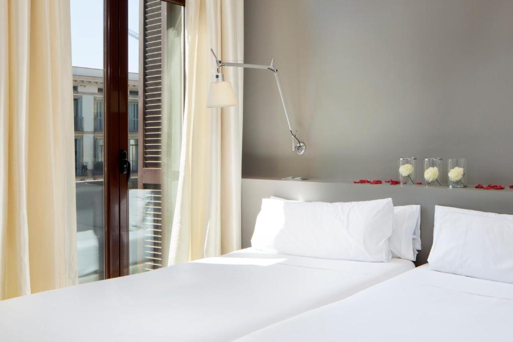 A bed or beds in a room at Hotel Internacional Ramblas Atiram