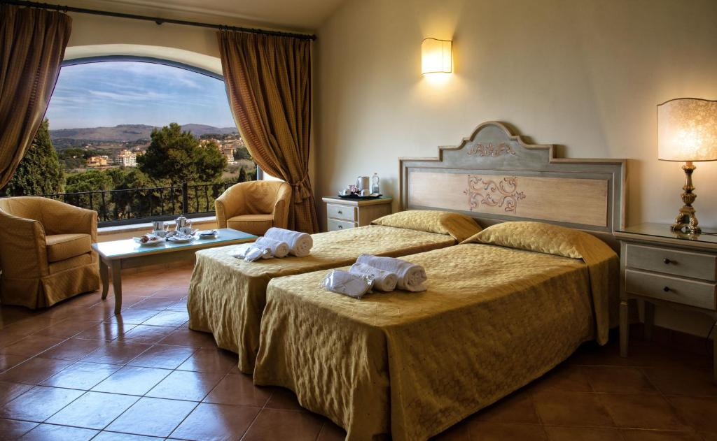 A bed or beds in a room at Grand Hotel Helio Cabala