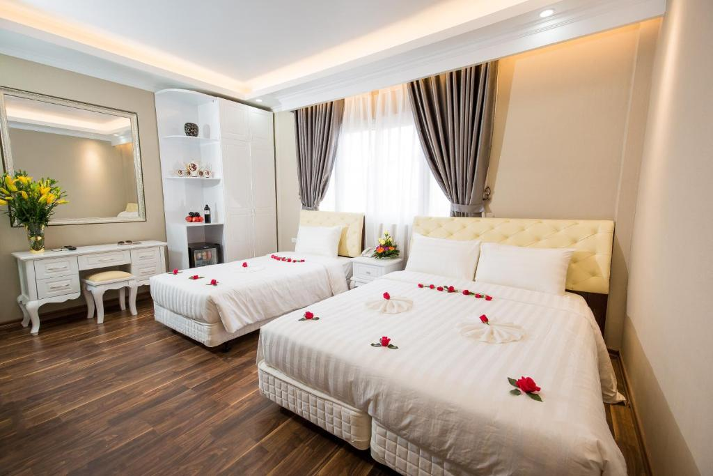 A bed or beds in a room at Little Hanoi Deluxe Hotel