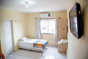 A bed or beds in a room at Hotel Pousada Delta Flat