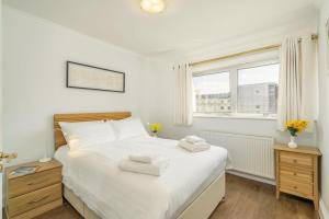 A bed or beds in a room at Three Bedroom Apt in Central London