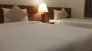 A bed or beds in a room at Green House Phuket