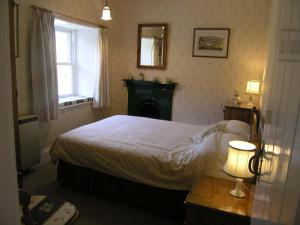 A bed or beds in a room at 3 Townhead Cottages