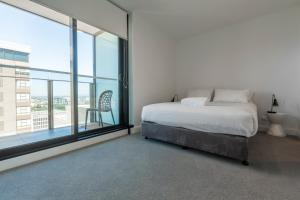 A bed or beds in a room at Apartments Melbourne Domain - CBD Paris End