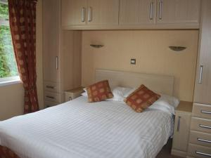 A bed or beds in a room at Barton Lodge, Pooley Bridge