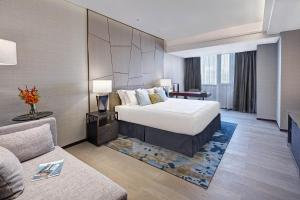 A bed or beds in a room at Fraser Suites Dalian