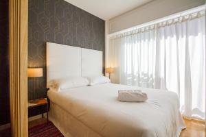A bed or beds in a room at UD Apartments - Atocha Stylish with pool