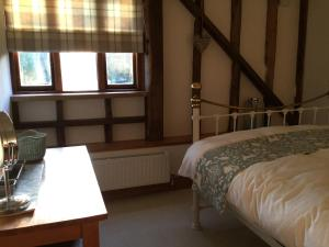 A bed or beds in a room at Heartwood Barn
