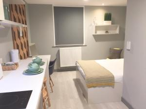 A bed or beds in a room at The Walls - Modern Studio Apartments