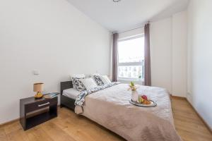 A bed or beds in a room at P&O Apartments Wola Park