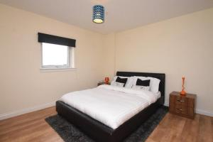 A bed or beds in a room at The Plaza Apartments (Great Location + Free Car Parking Near Glasgow City Centre)