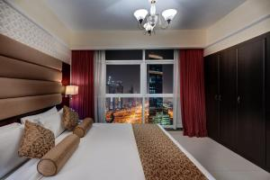 A bed or beds in a room at Emirates Grand Hotel Apartments