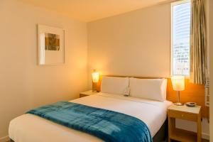 A bed or beds in a room at Astelia Apartment Hotel