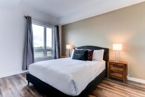 A bed or beds in a room at Kanata Lakes Apartments by Corporate Stays