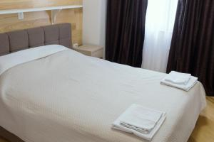 A bed or beds in a room at Trio Finest Skopje Apartments