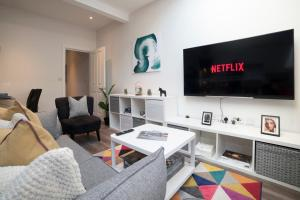 A television and/or entertainment center at Beautiful New 2 bed 1 bath - Arsenal Station