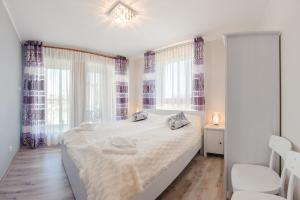A bed or beds in a room at Apartamenty Sun & Snow Aura
