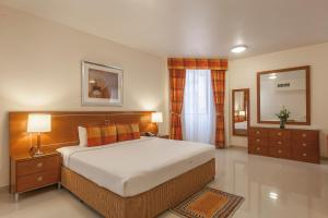 A bed or beds in a room at Golden Sands Hotel Apartments