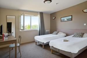 A bed or beds in a room at Appart'City La Roche sur Yon