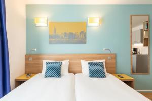 アパートホテル アダージョ アクセス ラ デファンス プラース キャラースにあるベッド