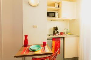 A kitchen or kitchenette at Appart-Hôtel Mer & Golf City Perpignan Centre