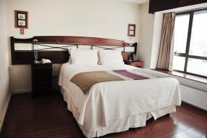 A bed or beds in a room at Apart Hotel Neruda