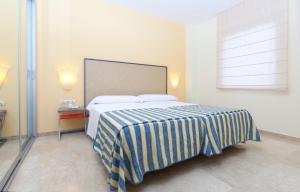 A bed or beds in a room at Apartamentos Vértice Sevilla Aljarafe