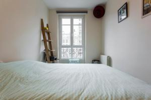 A bed or beds in a room at Typical Parisian flat near Belleville by easyBNB
