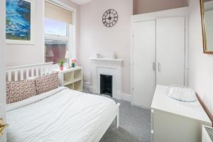 A bed or beds in a room at Cosy 3 Bed Sleeps 8 in Fulham 15 mins to Station