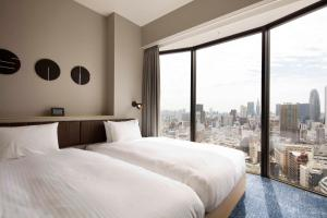 A bed or beds in a room at Hundred Stay Tokyo Shinjuku