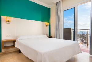 Een bed of bedden in een kamer bij Kn Aparthotel Panorámica