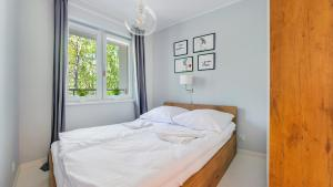 A bed or beds in a room at Apartamenty Sun & Snow Dwie Sosny