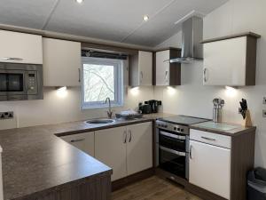 A kitchen or kitchenette at Riverside Rothbury Superior Lodge