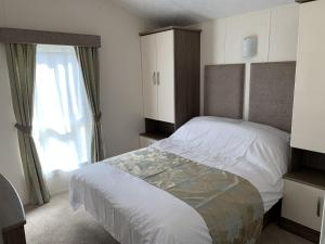 A bed or beds in a room at Riverside Rothbury Superior Lodge